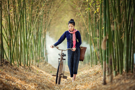Asian woman walk alone on an ancient bicycle. Stock Photo - 78761639