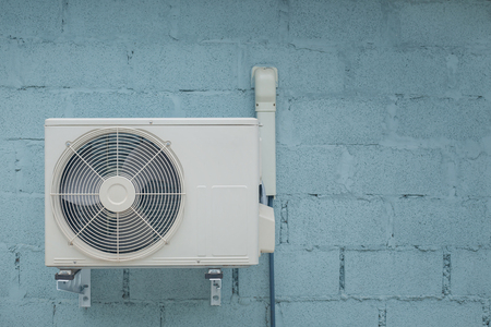 Condenser air conditioner with vintage brick background