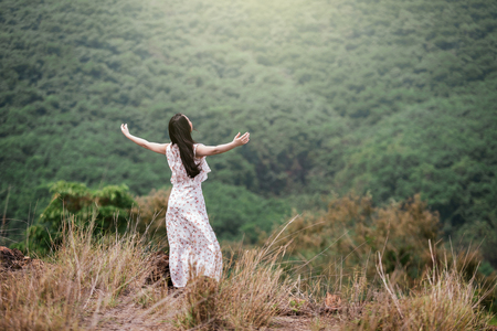 Carefree Happy Woman Enjoying Nature on grass meadow on top of mountain cliff with sunrise. Beauty Girl Outdoor. Freedom concept. Len flare effect. Sunbeams. Enjoyment. Banco de Imagens