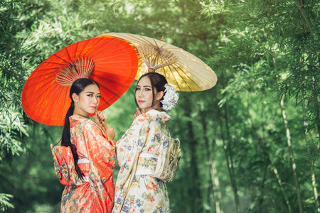 Asian girl wears a kimono and holds a traditional Japanese umbrella. Imagens - 106530587