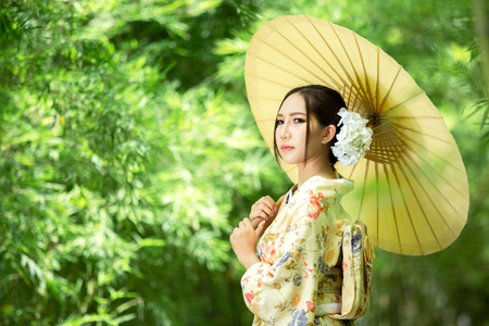 Asian girl wears a kimono and holds a traditional Japanese umbrella.