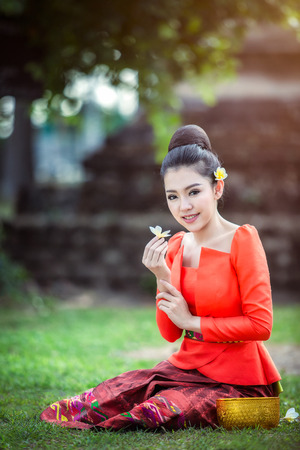 Happy young asian woman holding flower and sitting down on grass in the park