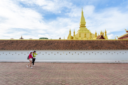 Two girlfriends traveling to Pha That Luang in vientiane,Laos Stock Photo