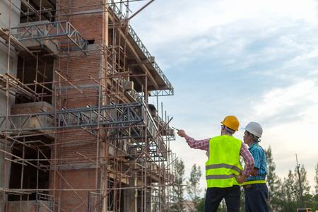 A construction worker control a pouring concrete pump on construction site. 스톡 콘텐츠