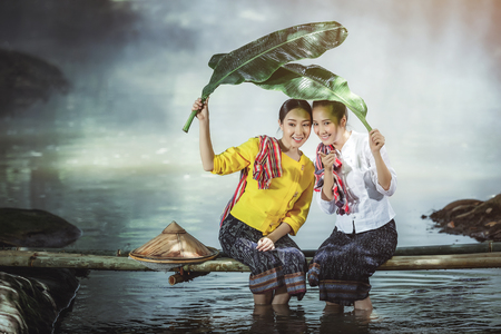 Two Asian beautiful girl plays the water in the river at Thailand, Concepts, colleagues and good friends. Banco de Imagens
