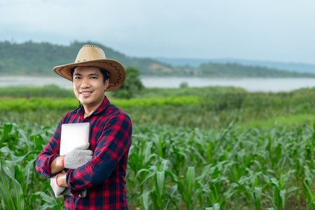 Young attractive farmer with laptop standing in corn field.