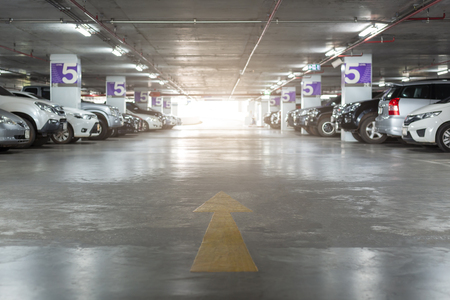 Blurred image of Underground parking with cars. White colors. Standard-Bild