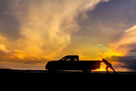 Man pushing a broken car down the road. Stock Photo