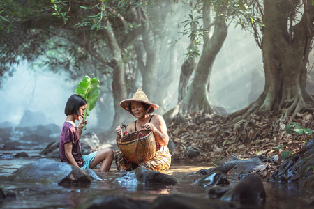 Asian Grandma and granddaughter catch crab in a basket in a stream in Thailand, Grandma teaches her granddaughter to survive.