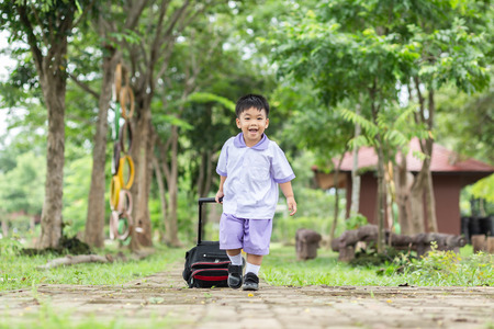 Asian little boy student walks his student bag back from school happily, Child Development Concept.