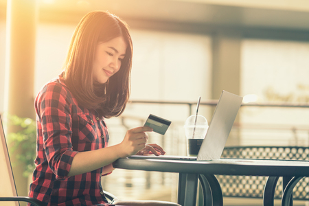 Asian woman using credit card shopping online in coffee shop vintage color tone.