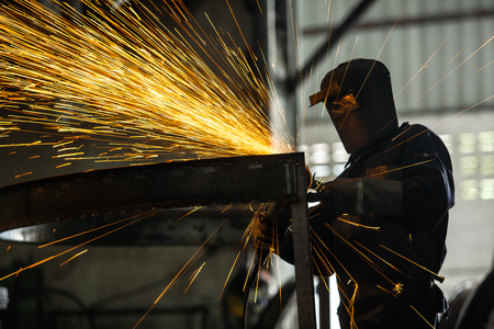 Masked workers and safety kits, Electric wheel grinding on steel structure and welders with multiple sparks in factory. Stock Photo