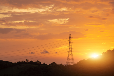 Electricity transmission power lines at sunset, High voltage tower. Archivio Fotografico