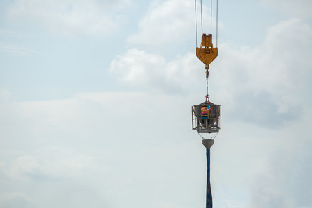 Construction worker on tower crane raised to pour concrete