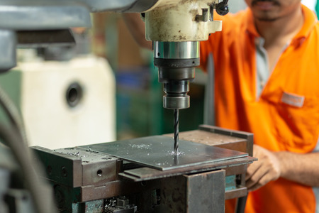 DRILLING MACHINE, Employee drilling machine in flat steel plate with bench drill. Stockfoto
