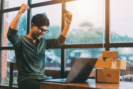 Young men delighted with the success of online sales, Online shopping young start small business in a cardboard box at work. The seller prepares the delivery box for the customer, online sales, or ecommerce. 스톡 콘텐츠