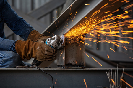 Electric wheel grinding on steel structure and welders with multiple sparks in factory.