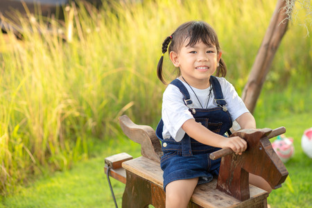 Asian little child girl riding on a wooden toy horse in the green grass garden.