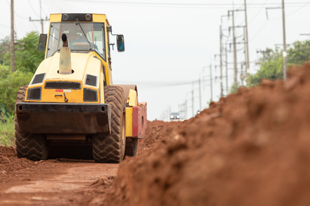 Yellow vibratory soil compactor working on highway construction site, Yellow vibratory soil compactor