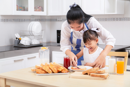 eating and people concept - Asian happy mother and daughter having breakfast at home. Stock Photo