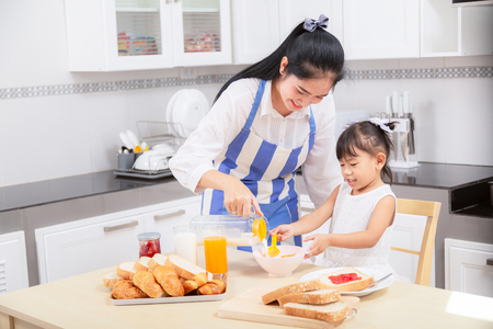 eating and people concept - Asian happy mother and daughter having breakfast at home. Banco de Imagens