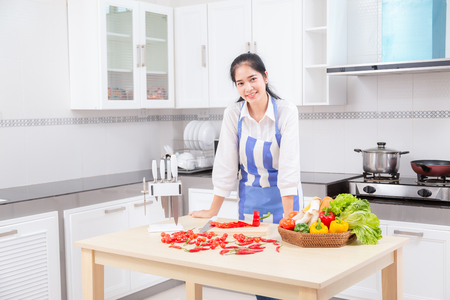 Asian beautiful young woman in cook is mixing batter, looking at camera and smiling while baking in kitchen at home