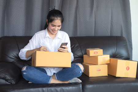 Asian girls get the order by phone, Online shopping young start small business in a cardboard box at work. The seller prepares the delivery box for the customer, online sales, or ecommerce. Banco de Imagens