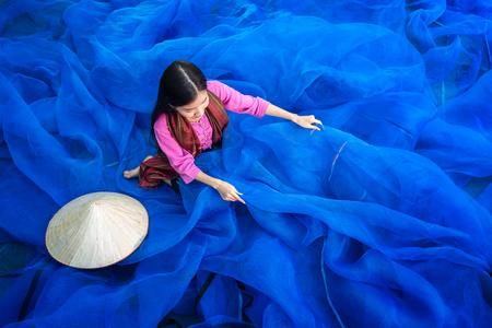 Beautiful woman fisherman is repairing fishing nets, Fisherman is cleaning Thai fishing nets,Thailand