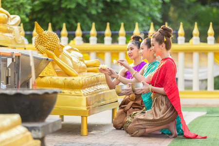 Asiatic woman are bathing Buddha statue happily in thailand.