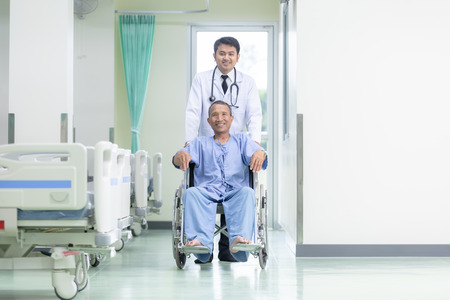 Asian patient in wheelchair sitting in hospital corridor with Asian male doctor, Medical equipment concept. Banque d'images - 110613170