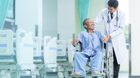 Asian patient in wheelchair sitting in hospital corridor with Asian male doctor, Medical equipment concept. Stock Photo - 110613171