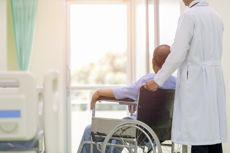 Asian patient in wheelchair sitting in hospital corridor with Asian male doctor, Medical equipment concept.