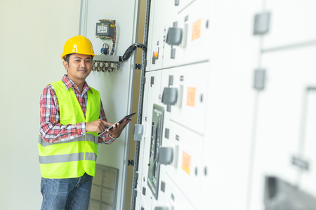 Asian maintenance engineers inspect relay protection system with laptop computer. Bay control unit. Medium voltage switchgear.