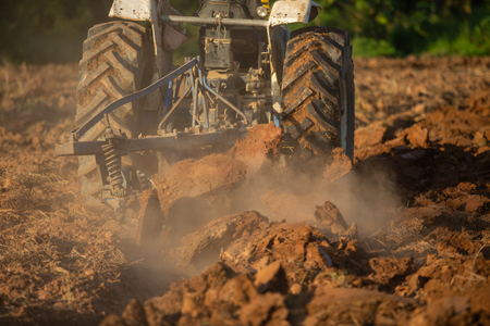 Asian agricultural workers use tractors to prepare soil for planting. Stok Fotoğraf - 110613231