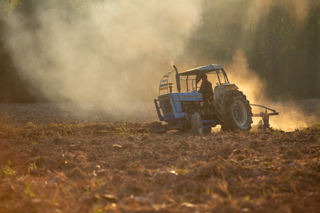 Asian agricultural workers use tractors to prepare soil for planting. Stok Fotoğraf - 110613234