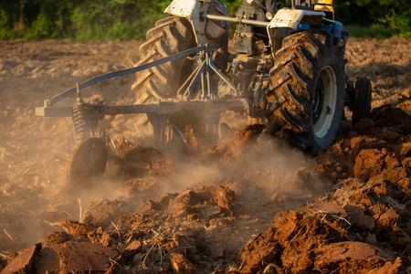 Asian agricultural workers use tractors to prepare soil for planting. Stok Fotoğraf - 110613237