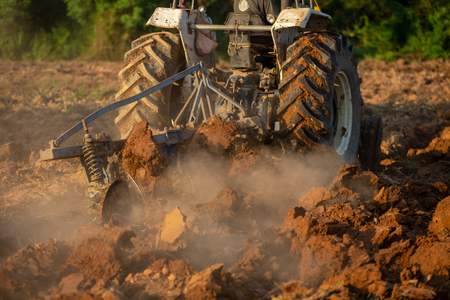 Asian agricultural workers use tractors to prepare soil for planting.