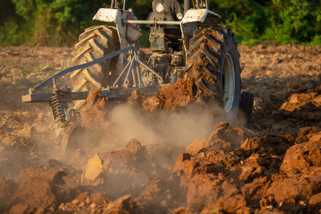 Asian agricultural workers use tractors to prepare soil for planting. Stok Fotoğraf - 110613239