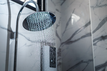 [shower head] shower head in bathroom with water drops flowing.