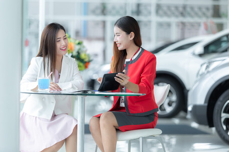 Asian auto business, car sale, technology and people concept - happy couple with car dealer in auto show or salon.