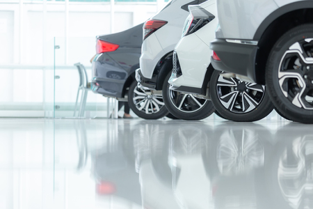 Cars For Sale, Automotive Industry, Cars Dealership Parking Lot. Rows of Brand New Vehicles Awaiting New Owners, on the epoxy floor in new car service Stockfoto