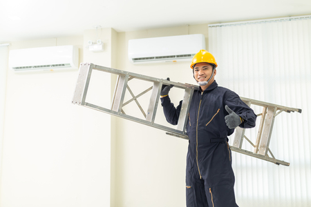 Male technician repairing air conditioner safety uniform indoors.