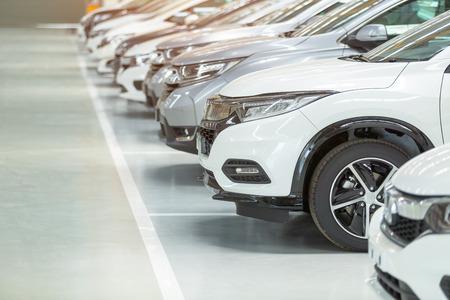 Auto in vendita, industria automobilistica, parcheggio di concessionarie auto. File di veicoli nuovi di zecca in attesa di nuovi proprietari, sul pavimento epossidico nel servizio di auto nuove