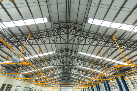 Steel roof truss in car repair center, Steel roof frame Under construction, The interior of a big industrial building or factory with steel constructions.