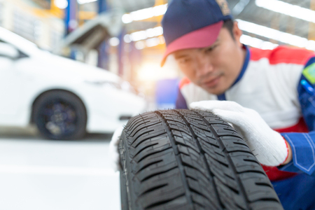 Asian man mechanic in uniform posing on spare wheel, Spare tire car, Seasonal tire change, Car maintenance and service center. Vehicle tire repair and replacement equipment. Stock fotó