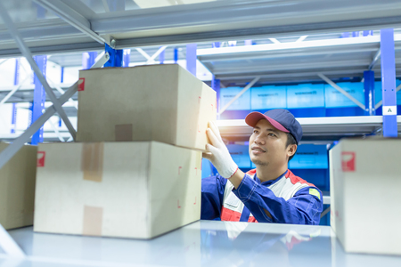 Asian man delivery staff in blue uniform work in warehouse keep goods, Auto mechanic is checking stock friendly worker in a warehouse and trade for car spare parts of a car repair shop. Stock fotó