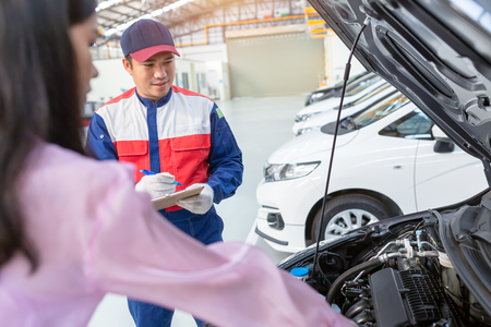 Asian car mechanic and customer Woman talking to a car mechanic in Car service center, both are standing next to the car.