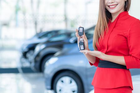 Cars For Sale, Beautiful Asian woman or car salesman Stand holding a new car remote key in the showroom.