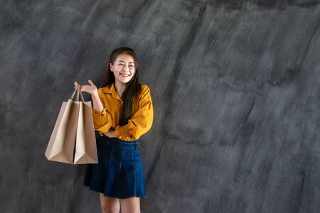Shopping Woman, Beautiful Asian well-dressed young irl holding a brown blank paper bag and makes purchases in an online store against a black wall background with copy space for text or design. Banco de Imagens
