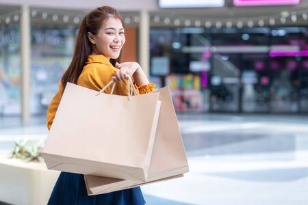 Asian Woman in shopping, Happy woman with shopping bags Paper bags reduce global warming enjoying in shopping. Consumerism, shopping, lifestyle concept.